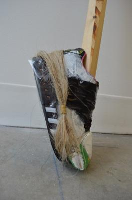 "Natalie Ball, ""Putter 2"", 2018, 7.4 ft. lodge pole pine tree, Air Max shoe, Adidas slipper, acrylic paint, sinew thread, beaded coin purse, horse hair, electrical tape"